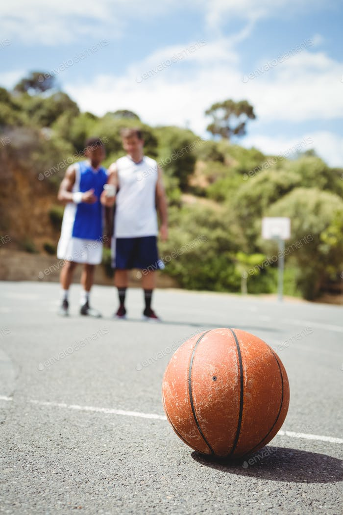 Basketball on ground with player standing in background