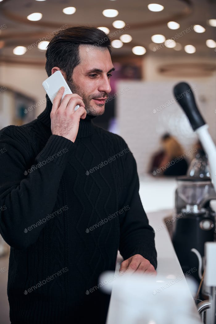 Handsome man talking on smartphone in restaurant