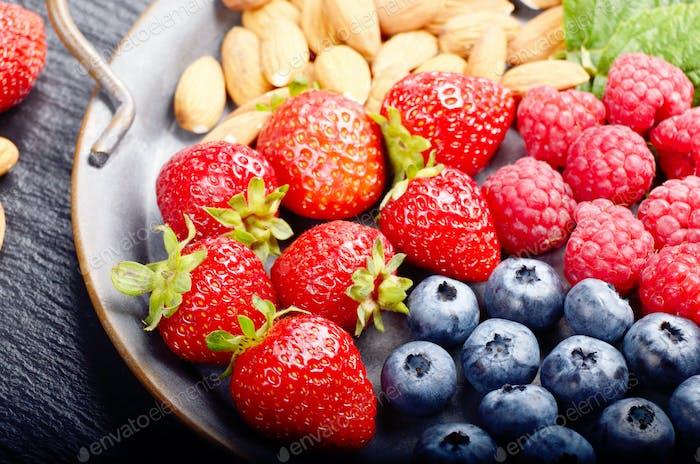 Tablett mit reifen BIO Heidelbeere Himbeere Erdbeere und Mandeln auf Schiefer Nahaufnahme