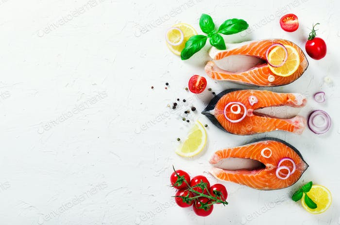 Raw fresh salmon steak with vegetables. Ingredients for cooking on white background. Space for text