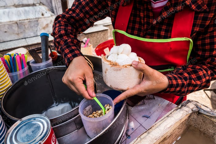 Serving fresh coconut ice cream in a coconut