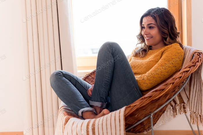 Woman sitting in  rattan chair at home