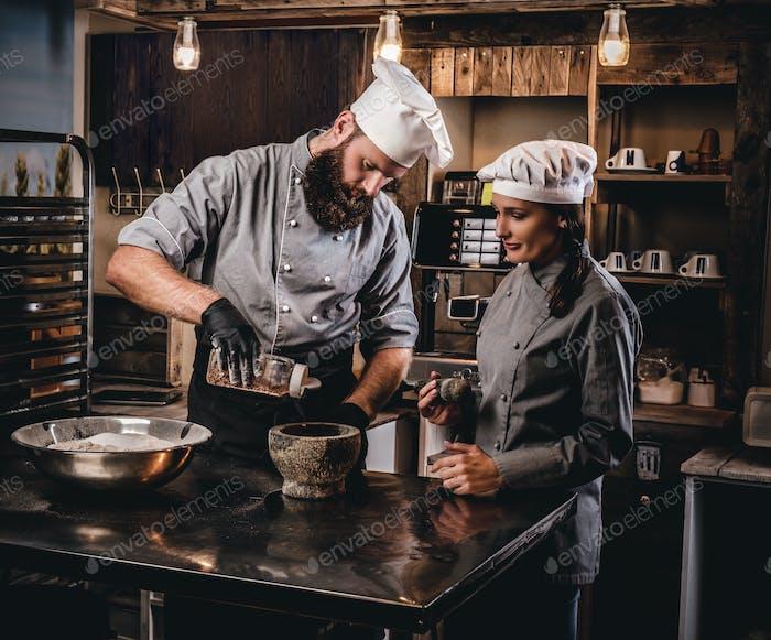 Chefkoch unterrichtet seinen Assistenten, das Brot in einer Bäckerei zu backen.