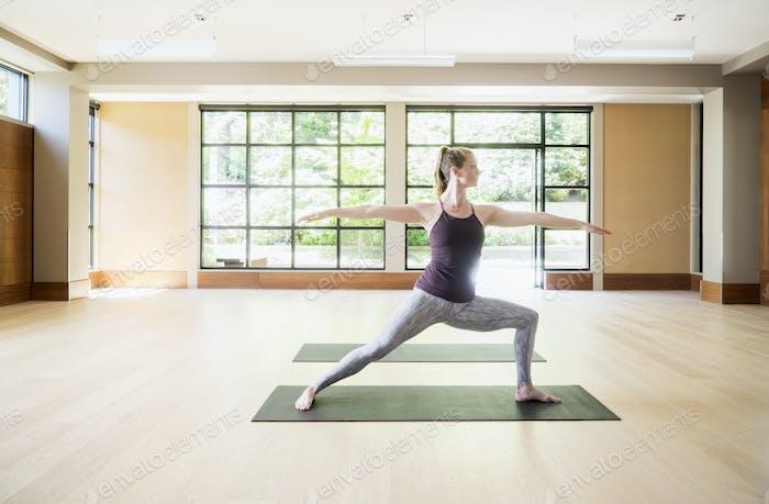 Mujer estirándose en posición de yoga en el gimnasio.