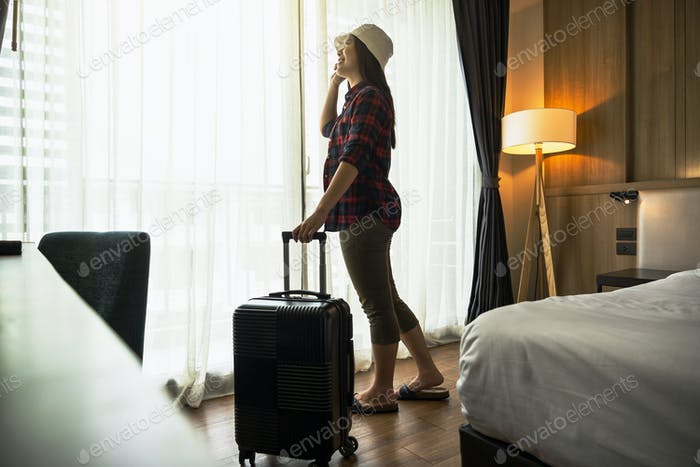Happiness Asian traveler woman standing with baggage in bedroom of hotel or hostel when traveling
