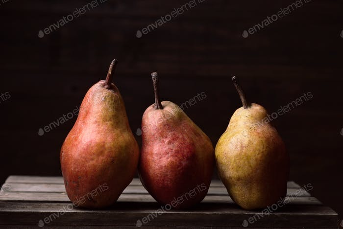 pears in row on rustic wooden boards in dark stage