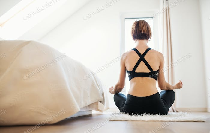 Rear view of young woman doing yoga exercise indoors in a bedroom. Copy space.