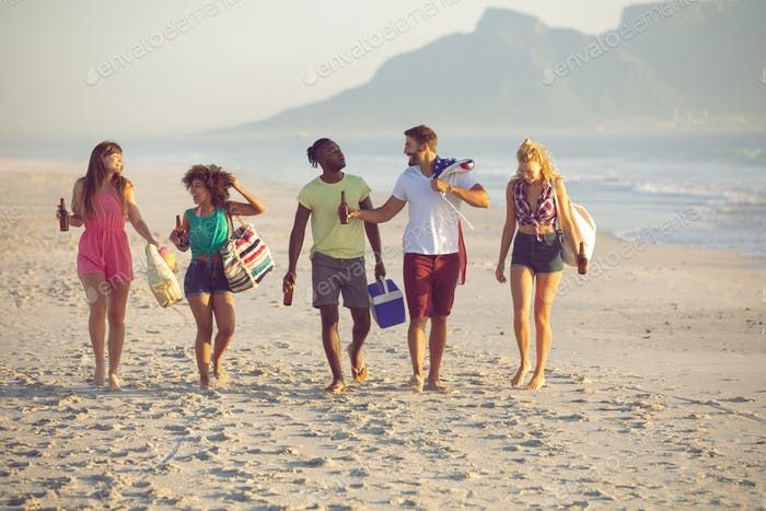 Front view of group of diverse friends walking together on the beach
