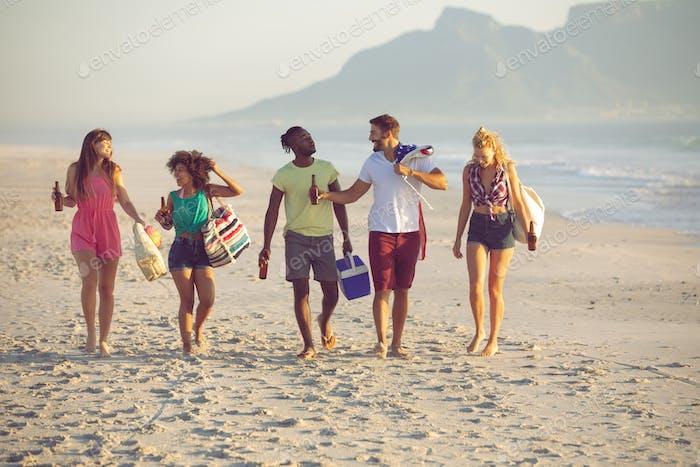 Vorderansicht der Gruppe von verschiedenen Freunden, die zusammen am Strand gehen