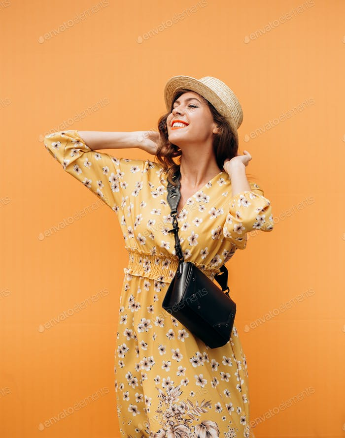 Beautiful girl dressed in a yellow long summer dress and hat poses against the background of an