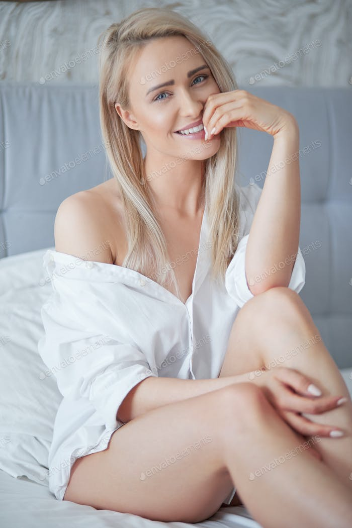 Beautiful young blonde woman in white shirt smiling at camera