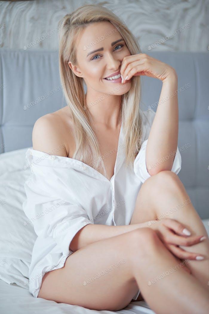 Schöne junge blonde Frau in weißem Hemd lächelnd bei Kamera