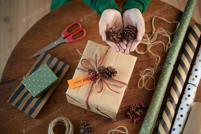 Crop person decorating box with pine cones