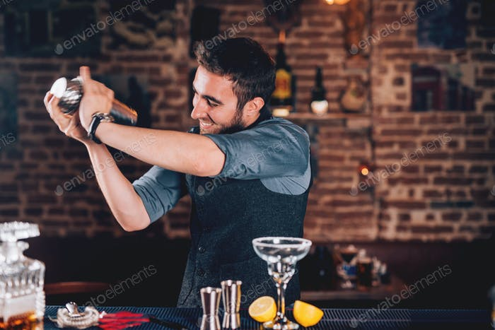 barman using shaker for cocktail preparation. Portrait of barman making tequila based margarita