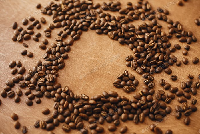 Coffee cup shape made in roasted coffee beans on wooden table