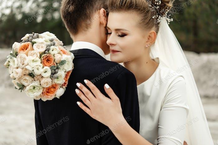 glückliche Braut umarmt stilvollen Bräutigam und lächelnd, zärtlichen Moment, Luxus-Hochzeit