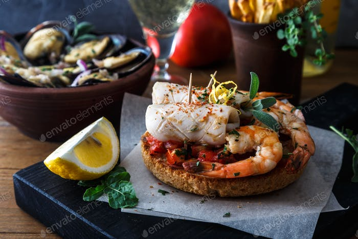 Appetizer with spicy tomato squids and shrimps on toast