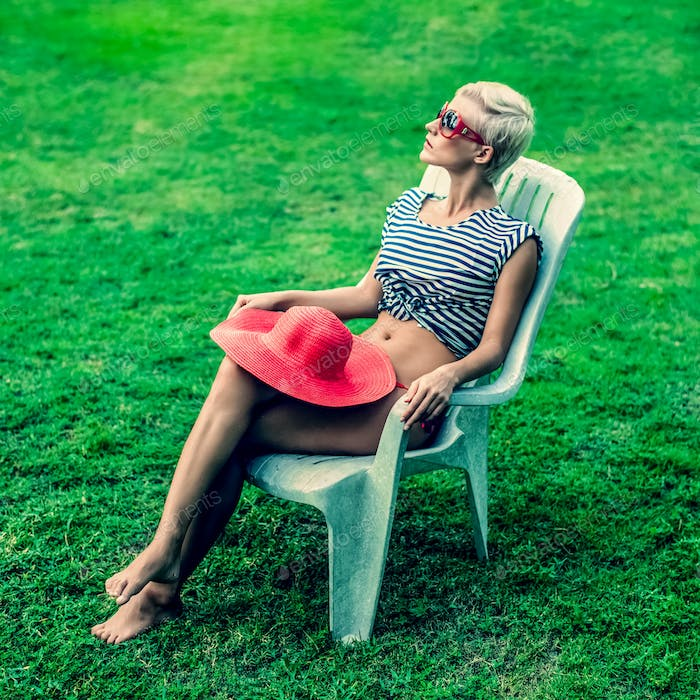 fashion girl sitting resting on a chair in the park