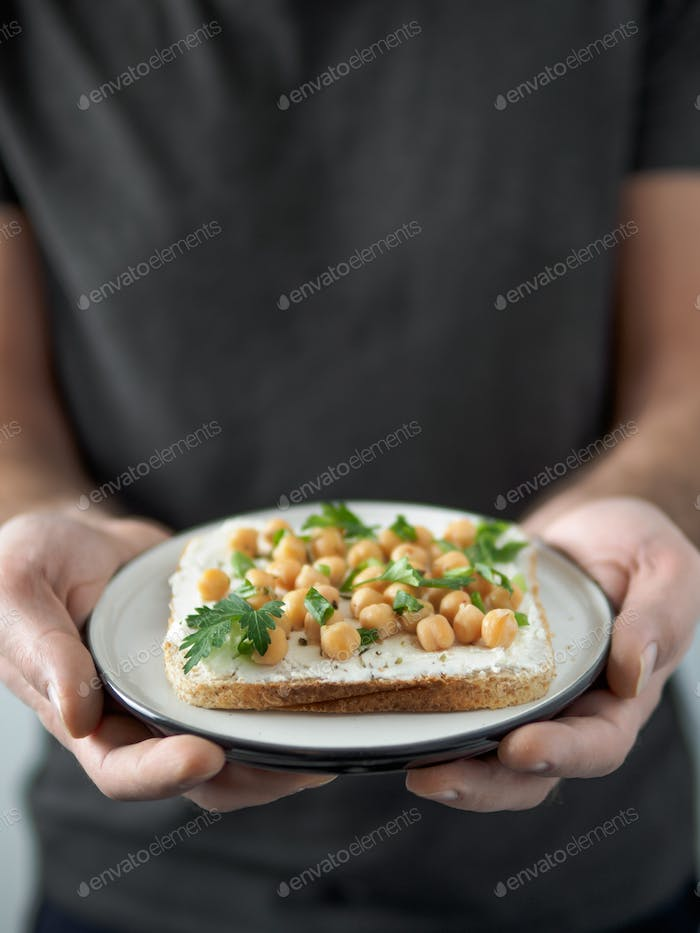 Vegan sandwich with chickpea in male hands