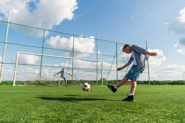 Boy playing soccer in the summer field