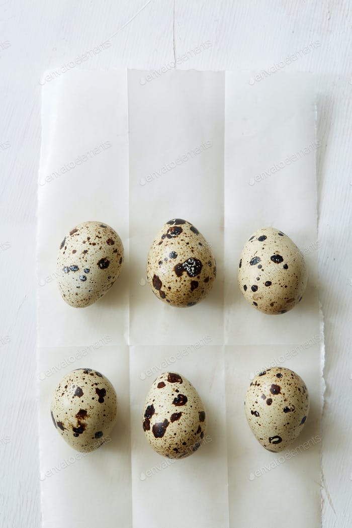 Flatview of quail eggs on white coocking paper
