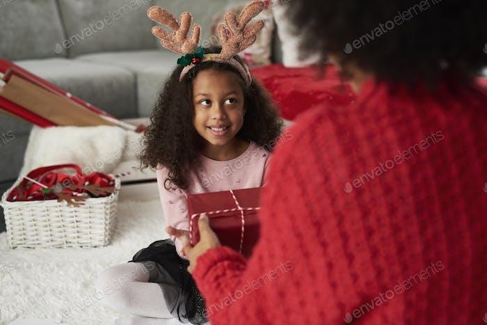 Rückansicht von Mama geben ihre Tochter das Weihnachtsgeschenk