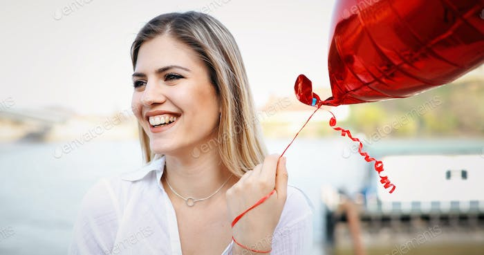 beautiful young woman with a heart-shaped balloon