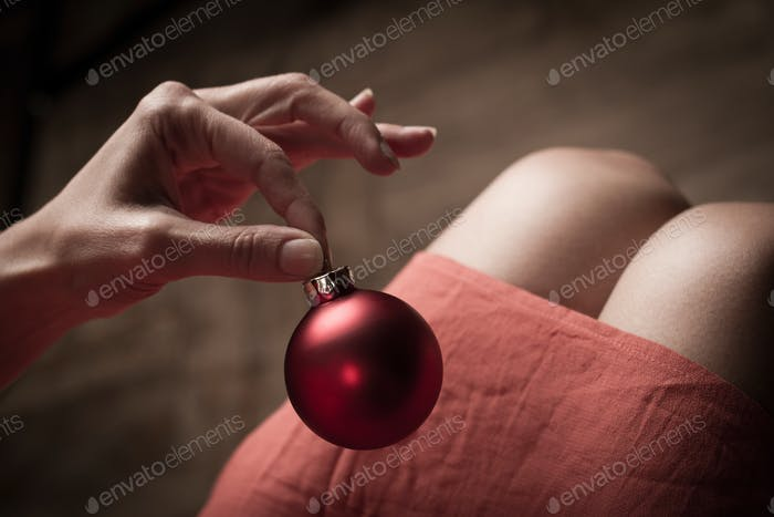 Woman holding a red Christmas globe