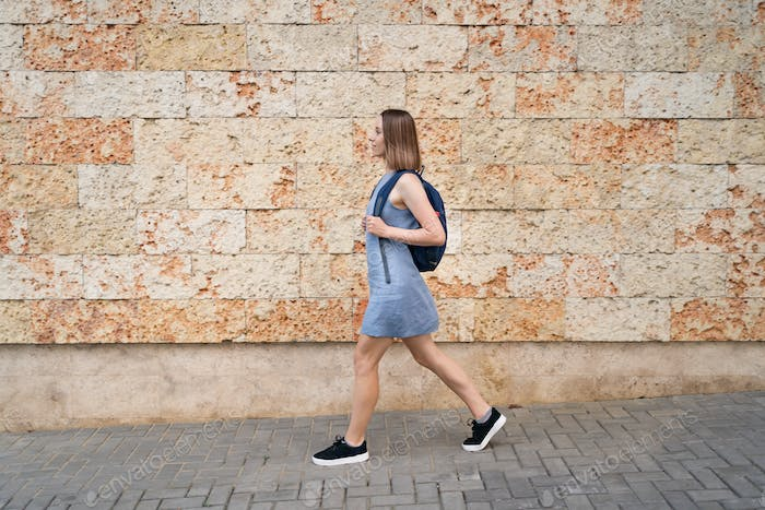 Young woman walking with backpack