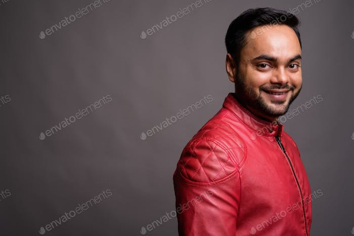 Young bearded Indian man against gray background