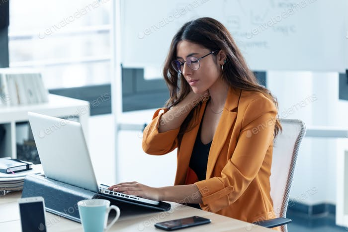 Business young woman with neck pain working with laptop in the office.