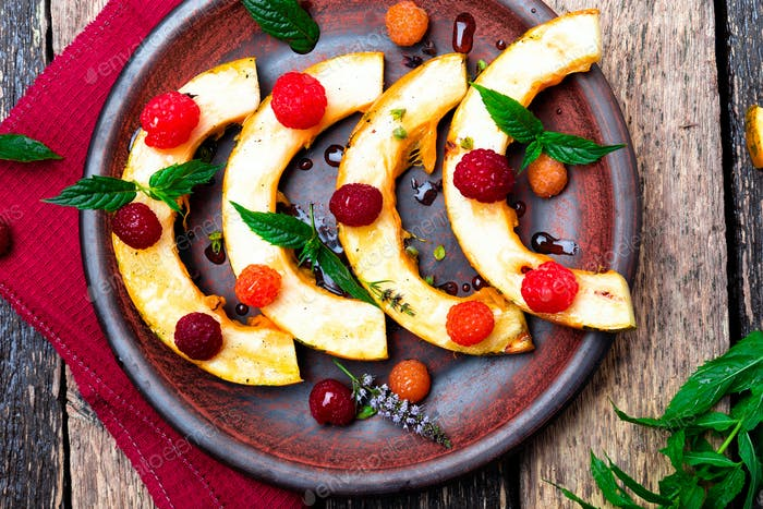 Grilled pumpkin with honey, raspberry and mint on wooden rustic background. Top view. Copy space.