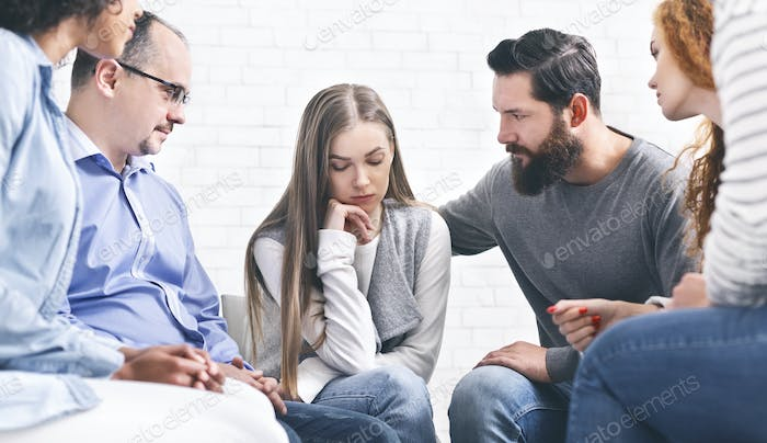 Patients comforting depressed woman at therapy session