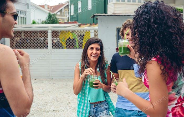 Glückliche Menschen mit Getränken, die im Sommerfest lachen