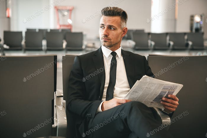 Serious businessman reading newspaper