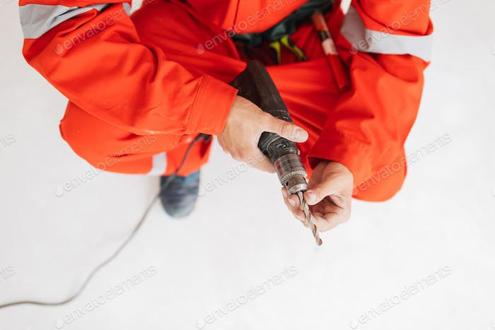 Close up foreman in orange work clothes holding drill machine in