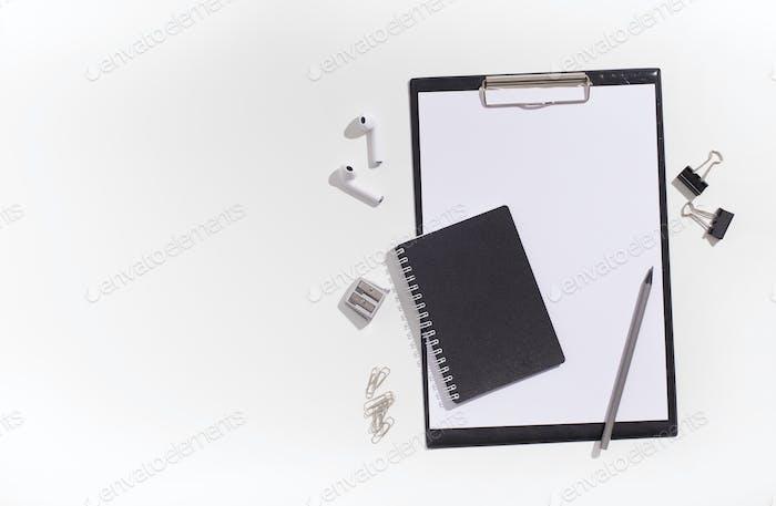 Black style supplies with earphones on white desktop
