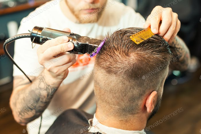 Young man having hair cutted