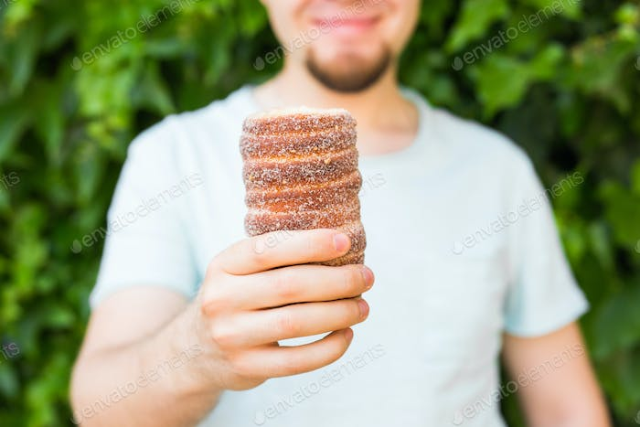 Trdelnik or trdlo in hand, national desert in Czech Republic.