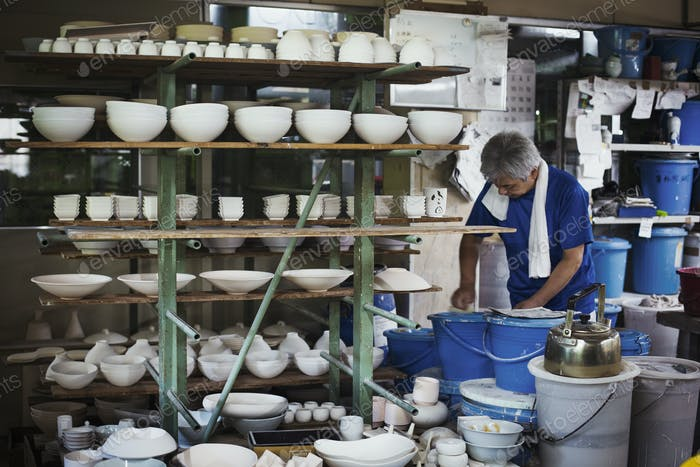 Man standing in a Japanese porcelain workshop with shelves of various porcelain bowls.