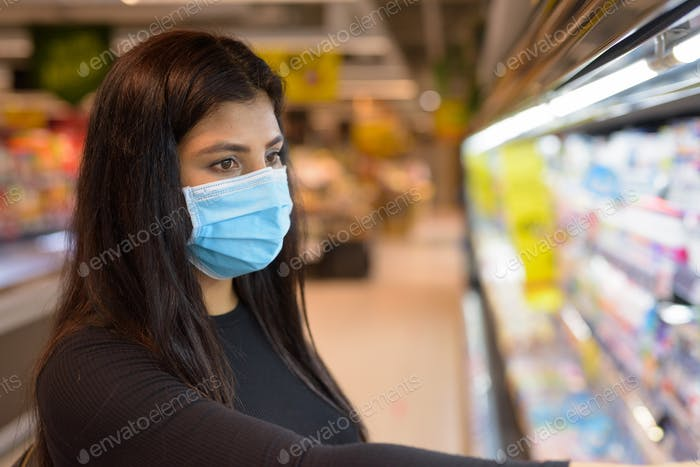 Face of young Indian woman with mask shopping with distance at the supermarket