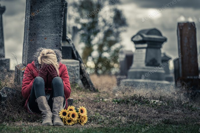 Lonely Sad Young Woman in Mourning in front of a Gravestone