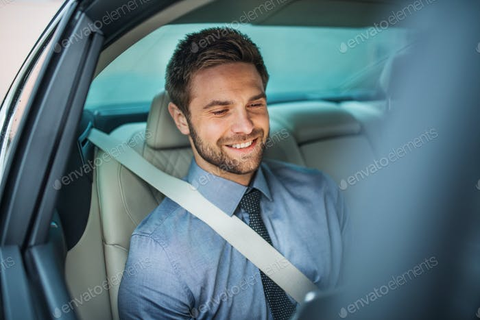 Businessman with tablet sitting on back seats in car, working