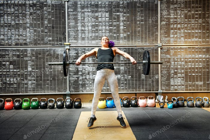 Young woman doing the snatch with a barbell