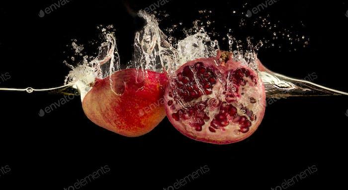 Granatapfel spritzt in Wasser vor schwarzem Hintergrund