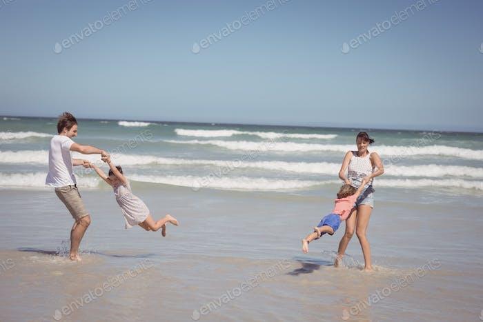 Alegre familia disfrutando en la orilla en la Playa