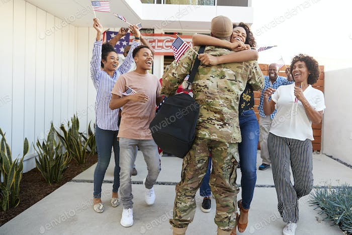 Excited three generation black family welcoming millennial soldier returning home,back view