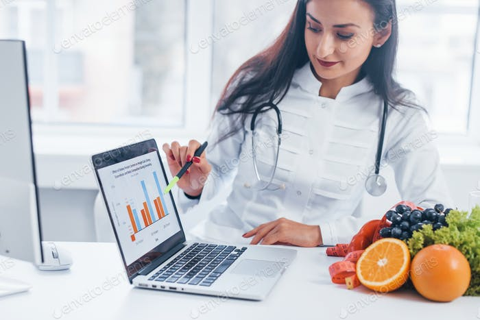 Female nutritionist in white coat sitting indoors in the office at workplace with laptop