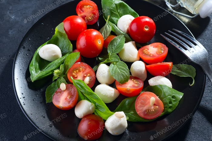 Tasty and beautiful Caprese salad on the black ceramic plate, close up