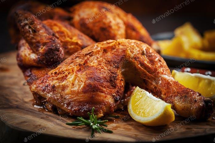 Würziges gegrilltes Huhn mit Zitrone auf hölzernem Hintergrund